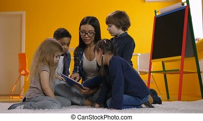Preschool teacher reading a book to diverse kids