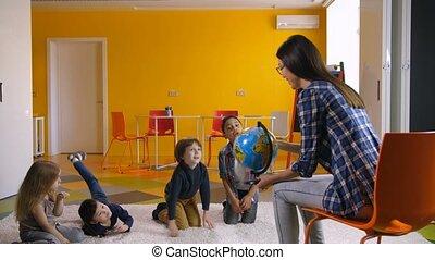 Preschool teacher teaching diverse kids about globe