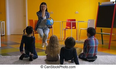 Preschool teacher teaching kids about globe - Preschool...
