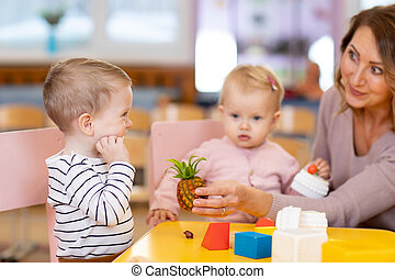 Preschool teacher with children playing with colorful toys at kindergarten