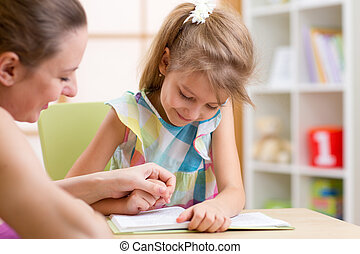 Preschooler Child Reading with Mother In Nursery at Home