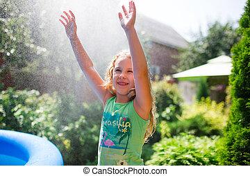 Preschooler cute girl playing with garden sprinkler. Summer outdoor water fun in the backyard.