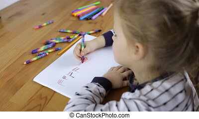 Preschooler girl draws flags of different countries with...