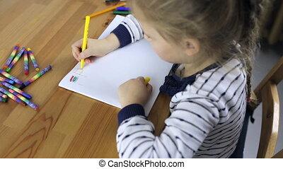 Preschooler girl draws flags with pencils in the album