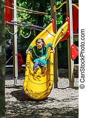 Preschooler girl sliding on a teeter board, new playground