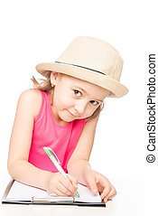 preschooler little girl wearing a hat at the table draws in a notebook isolated