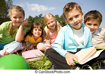 Portrait of smart preschooler holding book with his friends on background in natural environment