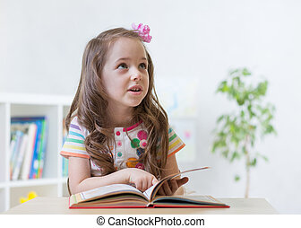 Preschooler smart girl reading book while sitting on chair in nursery