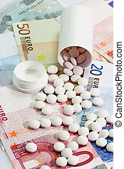 Prescription Charge - Open pill container with tablets on...