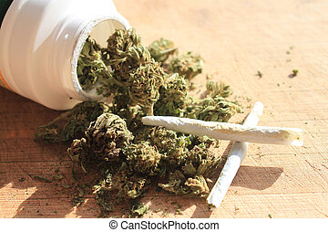Green prescription cannibis spilling out of a bottle with two joints