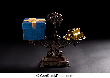 present box and gold bars on a balanced scale concept of expensive gifts