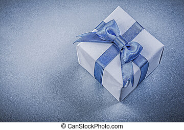 Present box with bow on blue background
