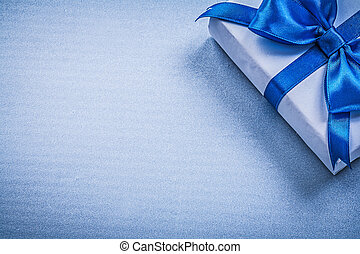 Present box with bow on blue background copyspace holidays...
