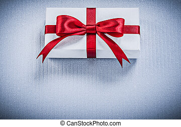 Present box with red bow on white background holidays concept