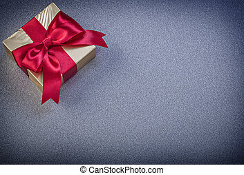 Present box with red knot on grey background holidays concept