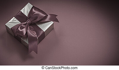 Present box with tied bow on red background holidays concept