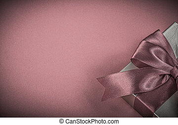 Present box with tied tape on red background holidays...