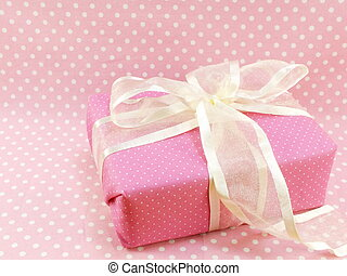 present gift box with pink polka dot background
