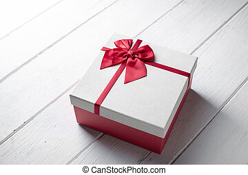 Present Gift Box With Red Ribbon On White Wooden Textured With Copy Space Use For Gift Event
