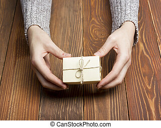 Present,  gift. Close up of female hands holding small gift