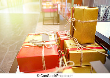 present gift in with red - gold wrapping paper and raw rope bow decoration.