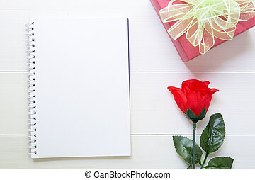 Present gift with red rose flower and notebook with copy space on wooden table, 14 February of love day with romantic, valentine holiday concept.