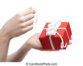 Gift opening. Wrapped in red paper present with white bow, isolated on white