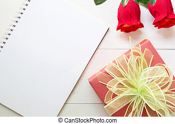 Present red rose flower and notebook and gift box with copy space on wooden table, 14 February of love day with romantic, valentine holiday concept.