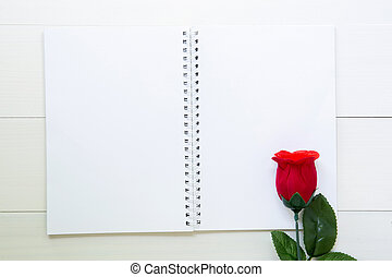 Present red rose flower and notebook with copy space on wooden table, 14 February of love day with romantic, valentine holiday concept, top view.