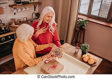 Two senior good-looking ladies opening a gift