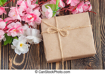 present with flowers bouquet on wooden background