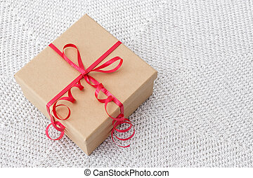 Present with red ribbon on a knitted background