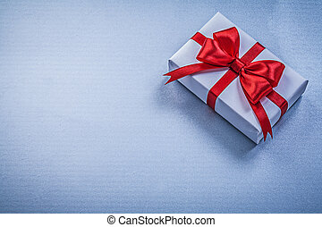 Present with ribbon on blue background holidays concept