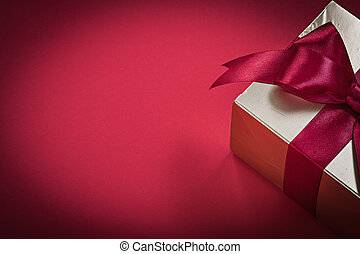 Present with tied bow on red background holidays concept