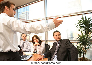 presentation - A group of four business people gather around...