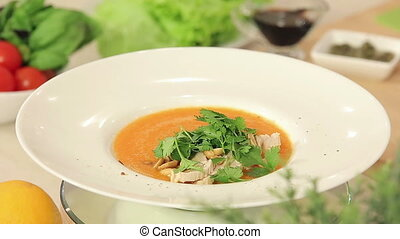 Presentation of Hot Carrot Cream Soup with Stewed Turkey Fillet and Fresh Parsley