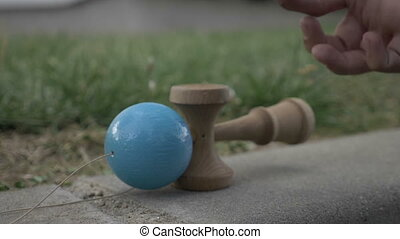 Presentation of kendama and fidget spinner outside in slow...