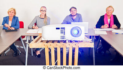 Presentation projector with an audience in a conference room...
