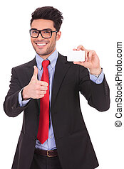 young business man presenting a blank card and showing thumbs up sign while smiling at the camera on a white background