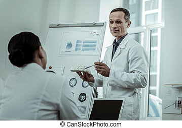 Couple of medical workers actively discussing brain disease