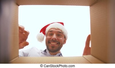 happy man opening parcel box or christmas gift - presents,...