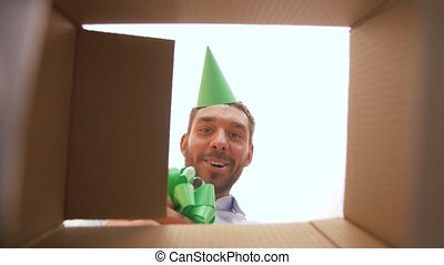 happy man opening parcel box or birthday gift - presents,...