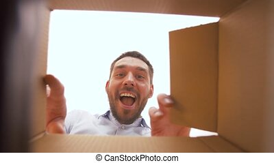 happy man opening parcel box - presents, delivery and...