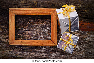 Wooden frame and gift boxes on wood table background.
