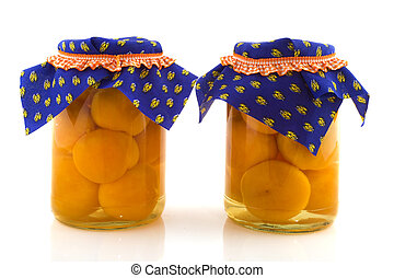 Preservated peaches in glass pots isolated over white background