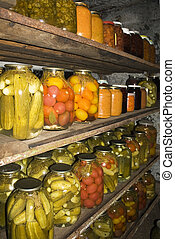 Homemade preserves sitting on to shelf in cellar. Pickles, tomatoes, cucumber, etc.