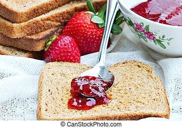 Preserves on wheat toast - Strawberry preserves being spread...