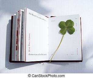 4-leaf-clover pressed in a booklet. The text tells in German: human is nothing else but what he makes out of himself - an aphorism by Jean-Paul Sartre. make the best - good luck!