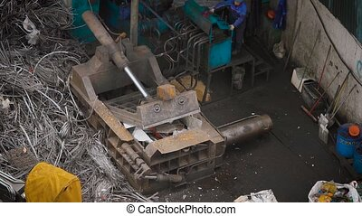 pressing machine is compressing metal scrap in a wrecking...