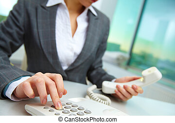 Pressing telephone buttons - Female hand holding phone...